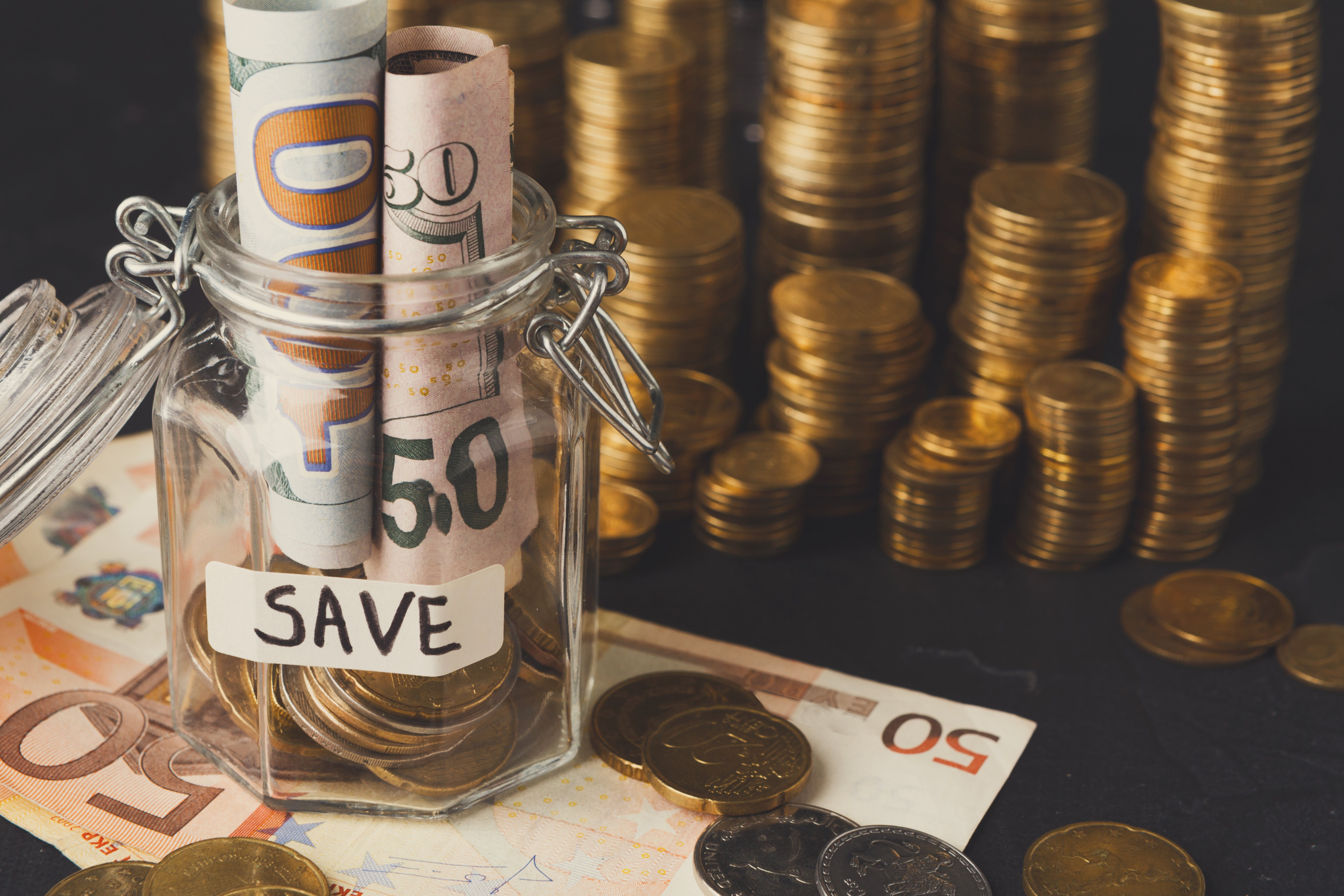Canva - Coins in glass jar for money saving, copy space