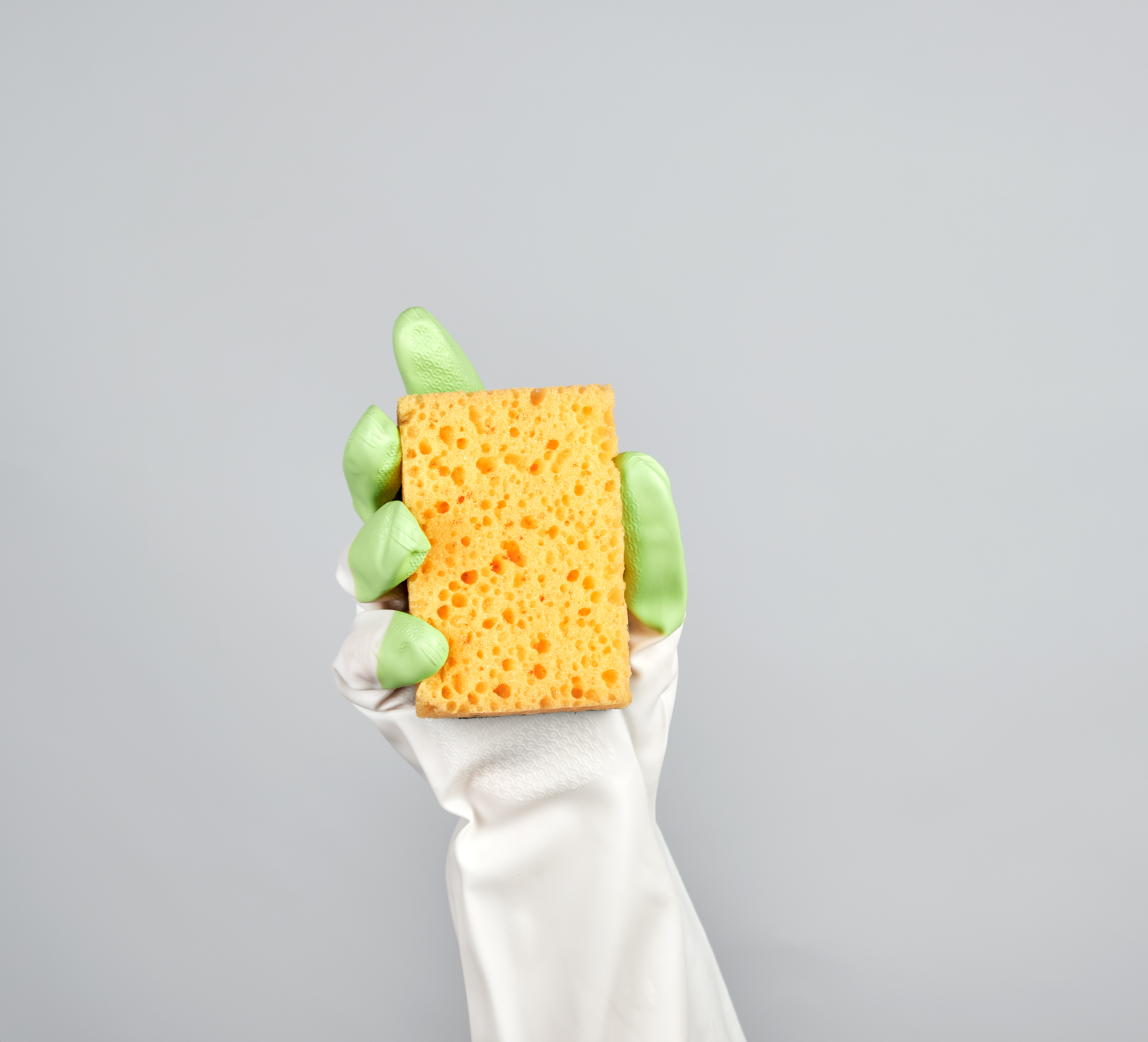 Canva - Gloved Hand Holding a Yellow Kitchen Sponge