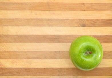 Canva - green apple sit on a worn butcher block cutting board