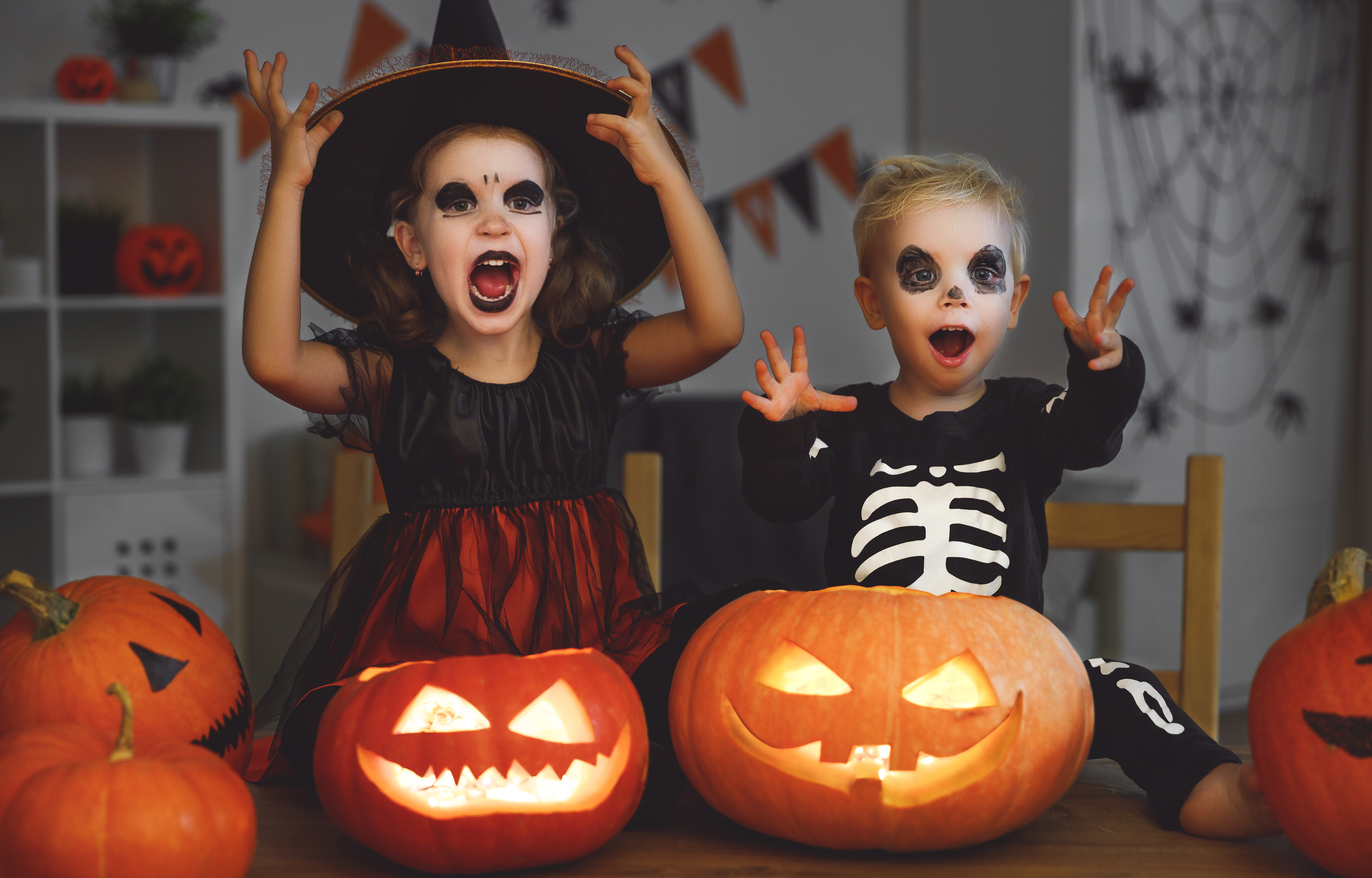 Canva - happy Halloween! children in costume of witch and skeletons with pumpkins and candles in dark (1)