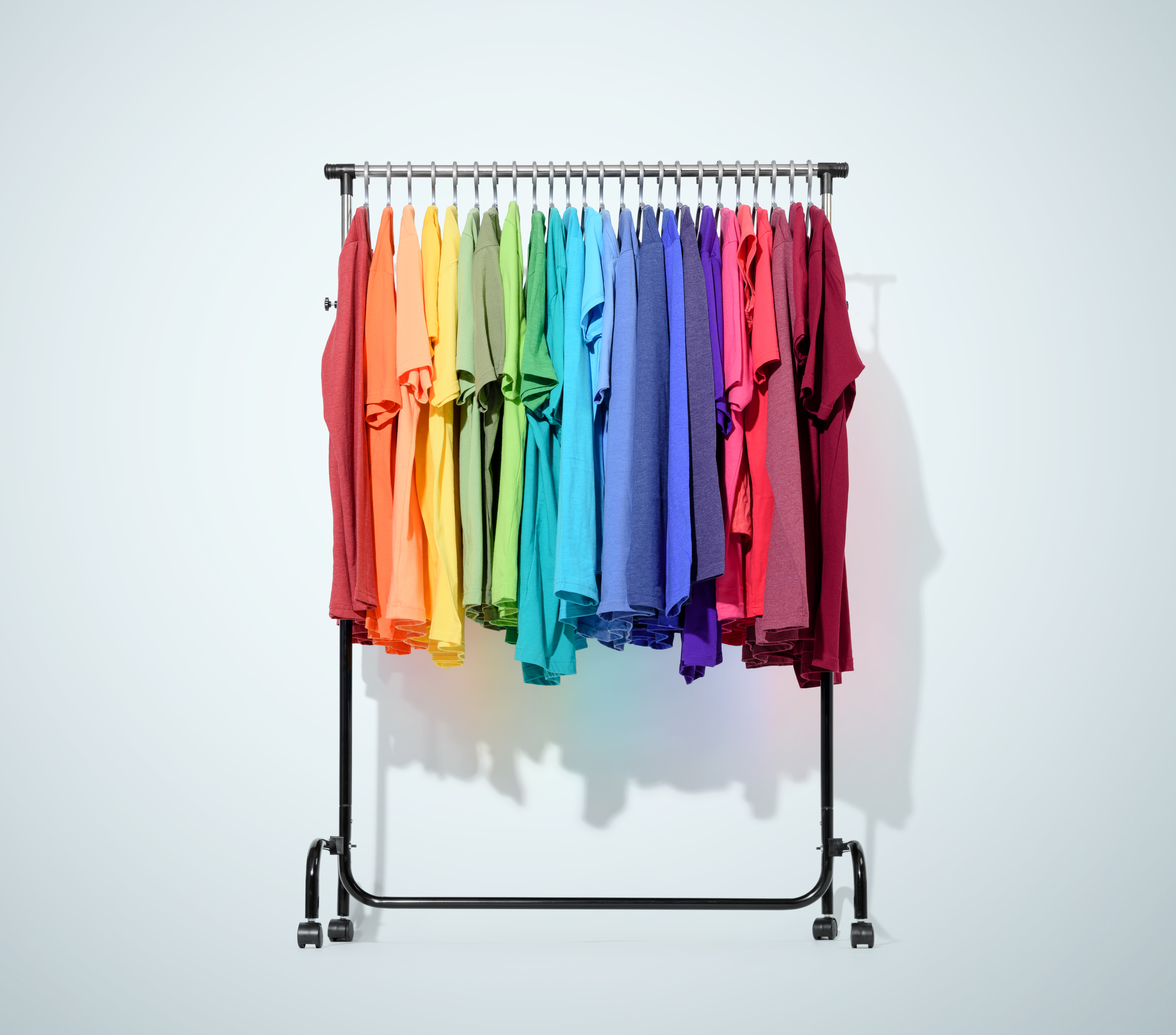 Canva - Mobile rack with color clothes on light blue background